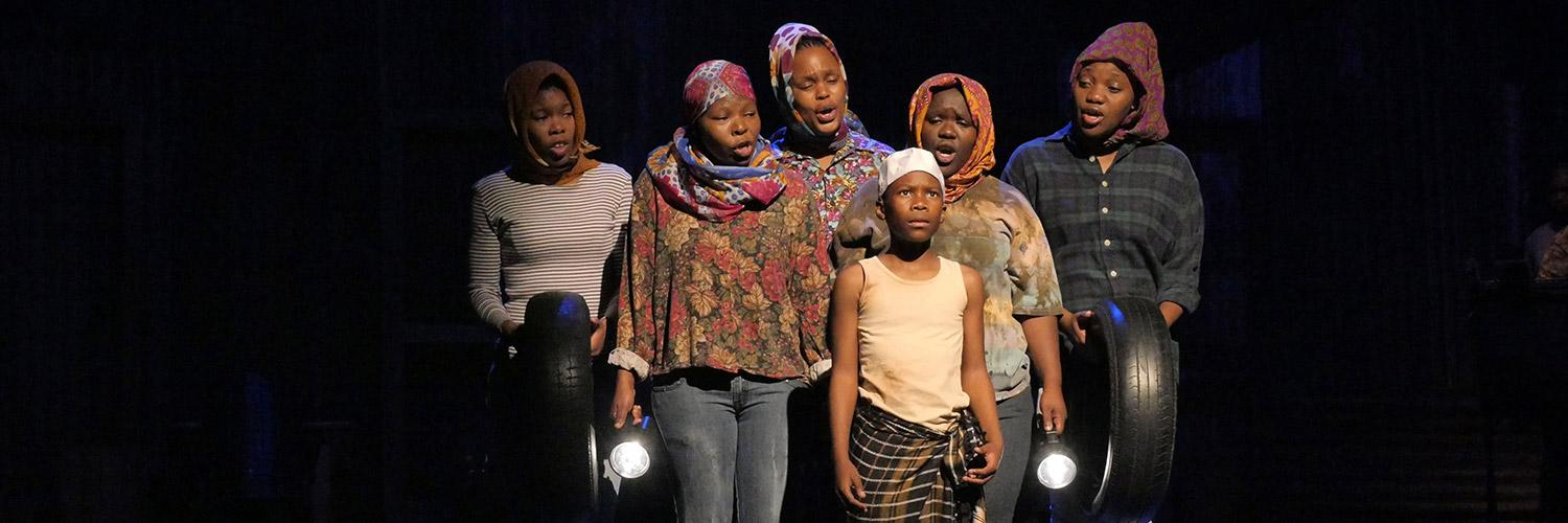 Five cast members of Isango Ensemble's A Man of Good Hope stand singing to the child actor on stage at the Young Vic. Photo by Keith Pattison.