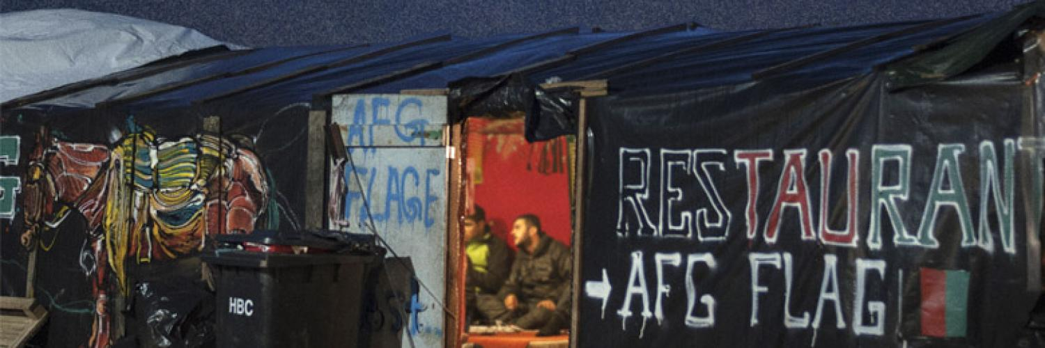 External photo looking into the dimly lit doorway of the temporary structure known as the Afghan Cafe in the Calais 'jungle' taken by  Giulio Piscitell