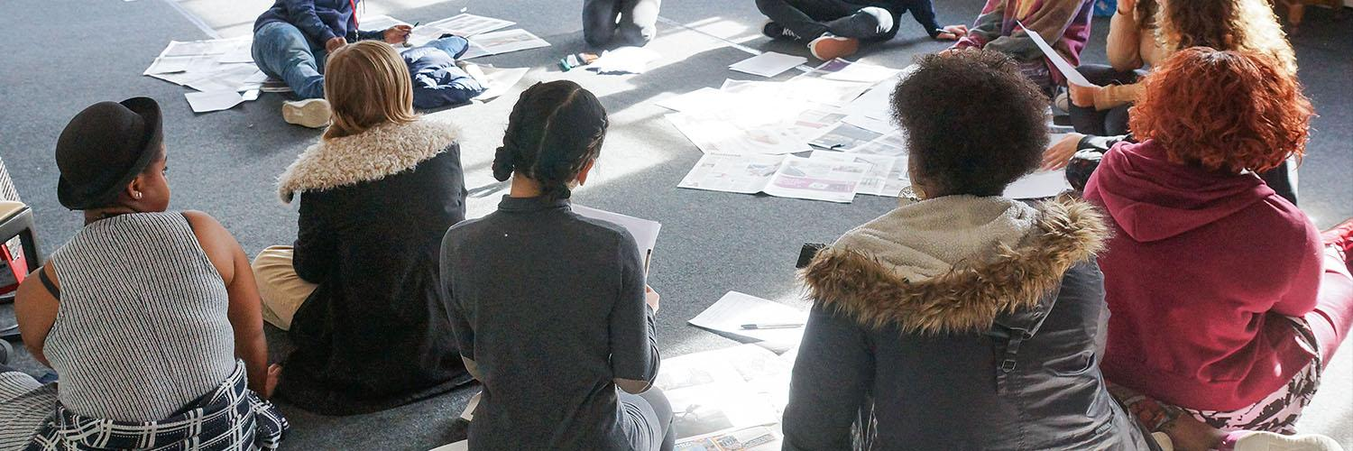 the backs of a group of people sitting on the floor surrounded by paper