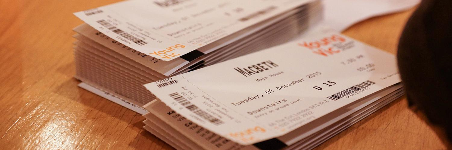Two stacks of Young Vic tickets sit on a desk. The name of the production and the Young Vic logo is in focus.