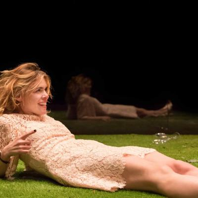 Billie Piper (Her) lies down on the grass, reclining in Yerma at the Young Vic by Johan Persson