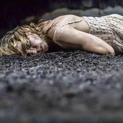 Billie Piper (Her) lies on her side, cold at wet on the mud in Yerma at the Young Vic by Johan Persson
