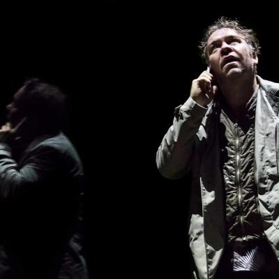 Brendan Cowell (John) talks on the phone and is reflected in the glass in Yerma at the Young Vic, photo by Johan Persson