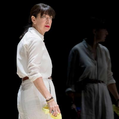 Maureen Beattie stands with a yellow cleaning cloth, reflected in the glass in Yerma at the Young Vic by Johan Persson