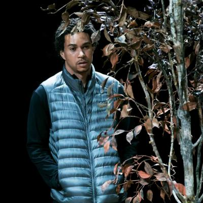 John McMillian (Victor) stands half obscured by a dying tree in Yerma at the Young Vic. Photo by Johan Persson