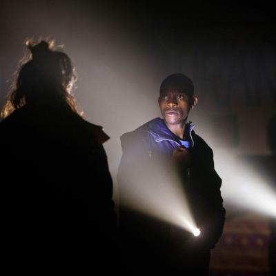 John Pfumojena (Okot) lit by torchlight in The Jungle at the Young Vic © David Sandison