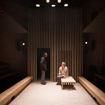 A wide angle shot looking down the traverse stage towards Jonathan Cullen (Man) who is wearing a suit almost standing over Maisie Greenwood (Woman) who is sitting on a bench in Winter at the Young Vic © Ellie Kurttz