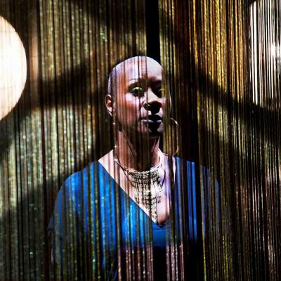 Josette Bushell-Mingo in Nina with beautiful fringed curtains and show lights behind her. Photo by Simon Annand
