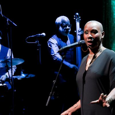 Josette Bushell-Mingo in front of two band members. Photo by Simon Annand