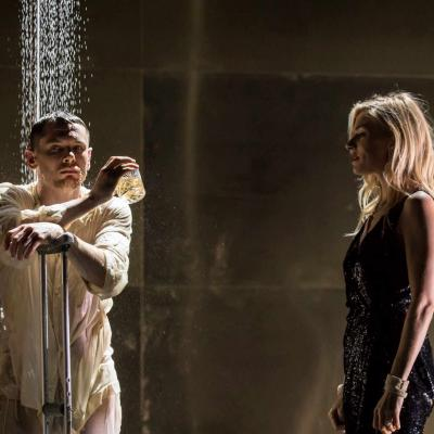 Jack O'Connell (Brick) stands under a shower with a crutch and Sienna Miller (Maggie) watches him in Cat on a Hot Tin Roof