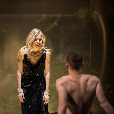 Sienna Miller (Maggie) and Jack O'Connell (Brick) who is leaning with his back to us on a bed in Cat on a Hot Tin Roof