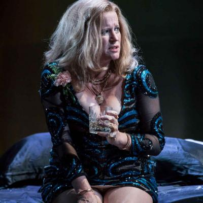 Lisa Palfrey (Big Mama) sits on a bed with a whiskey glass Cat on a Hot Tin Roof