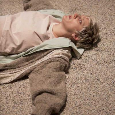 Maisie Greenwood (Woman) laying on a gravel floor onstage wearing a beige jacket, eyes staring into the sky in Winter at the Young Vic © Ellie Kurttz