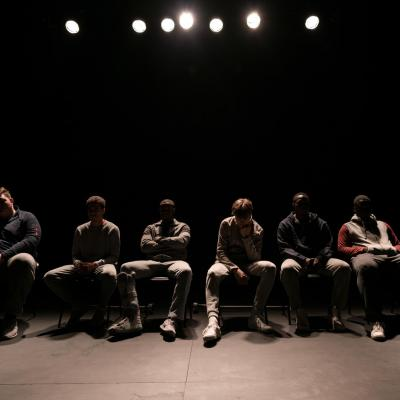 The group of six male actors sit backlit on their seats at the far end of the stage. We are not able to see any of their faces but their body language is negative, seemingly annoyed or put out © Leon Puplett