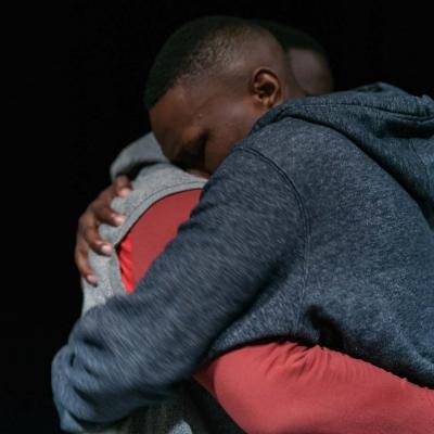 Two male performers embrace © Leon Puplett