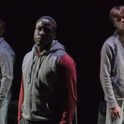 A man in a red and grey hoodie stands half in light with a solemn expression looking out to the audience as two other make performers stand either side of him a few feet behind him © Leon Puplett