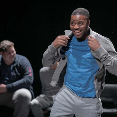 A grinning male performer adjusts the collar his hoodie, beaming out to the audience © Leon Puplett