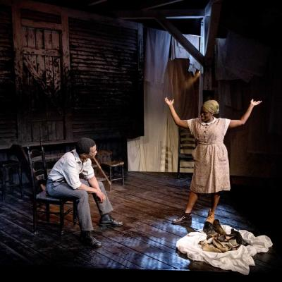 Production photo of Things of Dry Hours. The set is dimly lit with dark wooden floorboards and a dirty wooden slated backdrop. Washing hangs in the background. The actors wear basic 1900s era working dress.