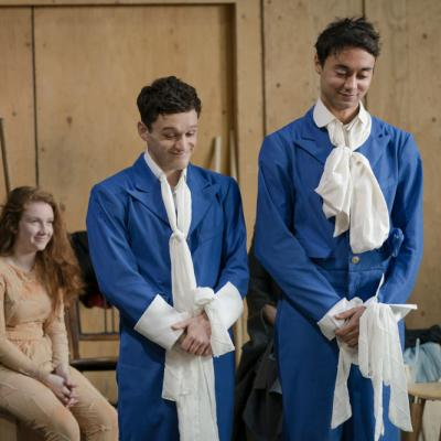 Two male actors stand smiling whilst rehearsing a scene. They're dressed in blue jumpsuits with long white collars © Leon Puplett