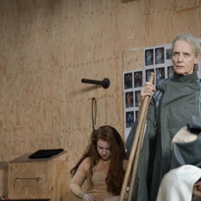 A female actor in long grey overalls stands solemn faced, holding a broom waiting for a scene to start © Leon Puplett