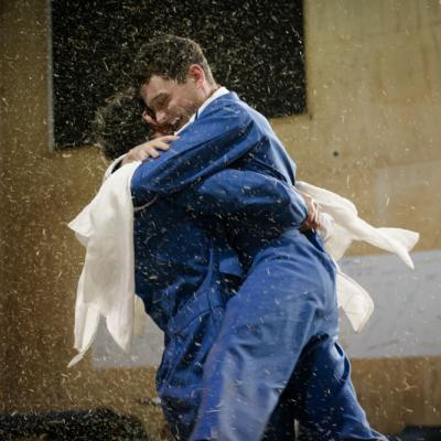 Two male actors embrace one another whilst spinning on the spot as hay rains down all around them © Leon Puplett