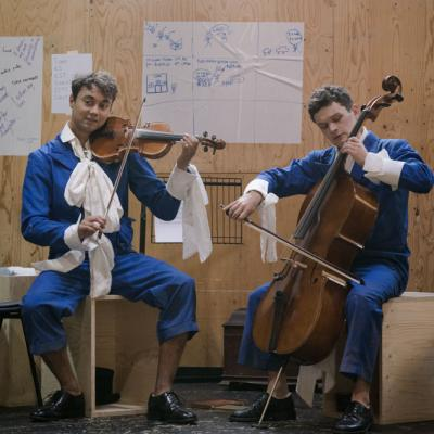 Two male actors sit in their blue jumpsuits with white collars. One is playing a violin, the other a cello © Leon Puplett