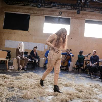 A young female actor crosses the stage, stuffing hay into the belly of her skin coloured outfit © Leon Puplett