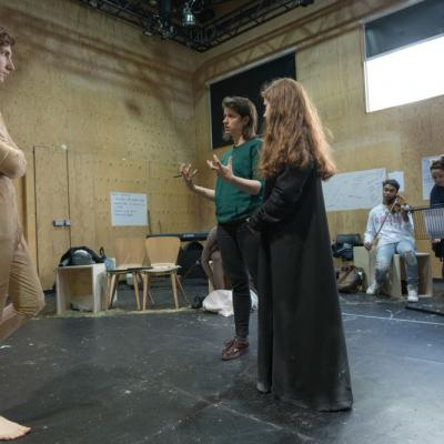 Director Caroline Byrne gives notes on a scene to a young male and female actor whoi stand either side of her © Leon Puplett