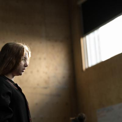A young female actor is staring off into the distance as she stands on the left of frame, lit by natural light through a window above her © Leon Puplett
