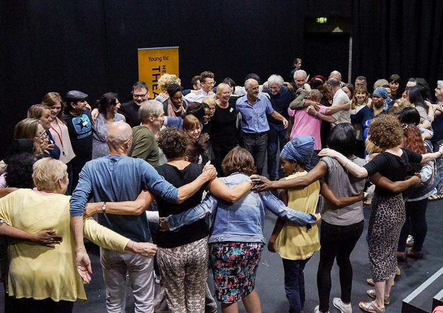 People standing in a circle in a workshop with their arms around each other.
