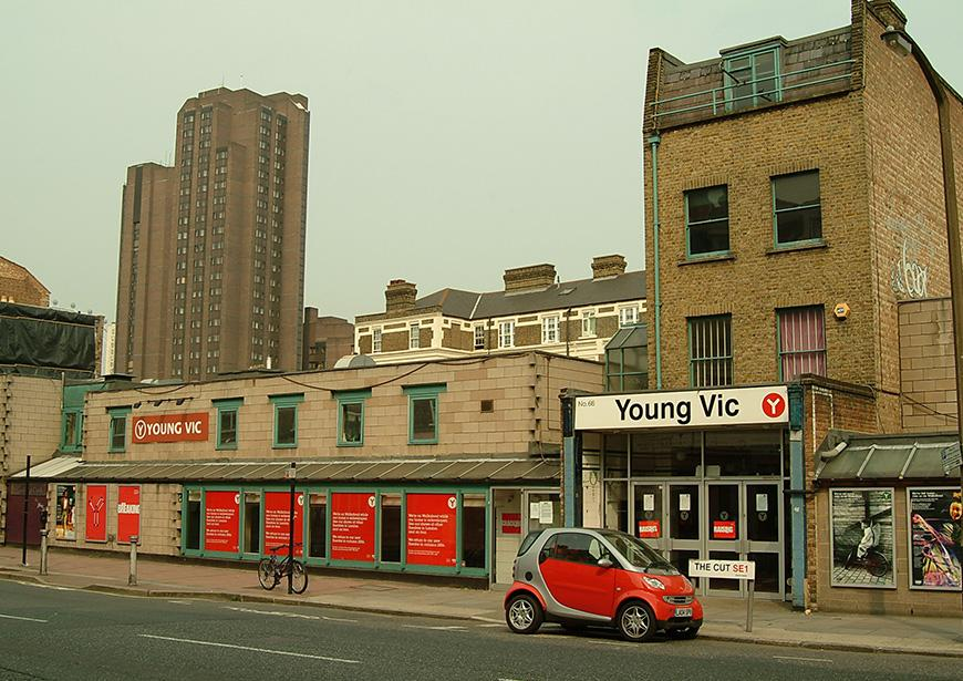 A photo of the Young Vic before it's rebuild in 2006. The old red YV branding covers the walls of the low slung building with the old house that was once a bakery at the East end of the building. A red Smart car sits outside the box office entrance.