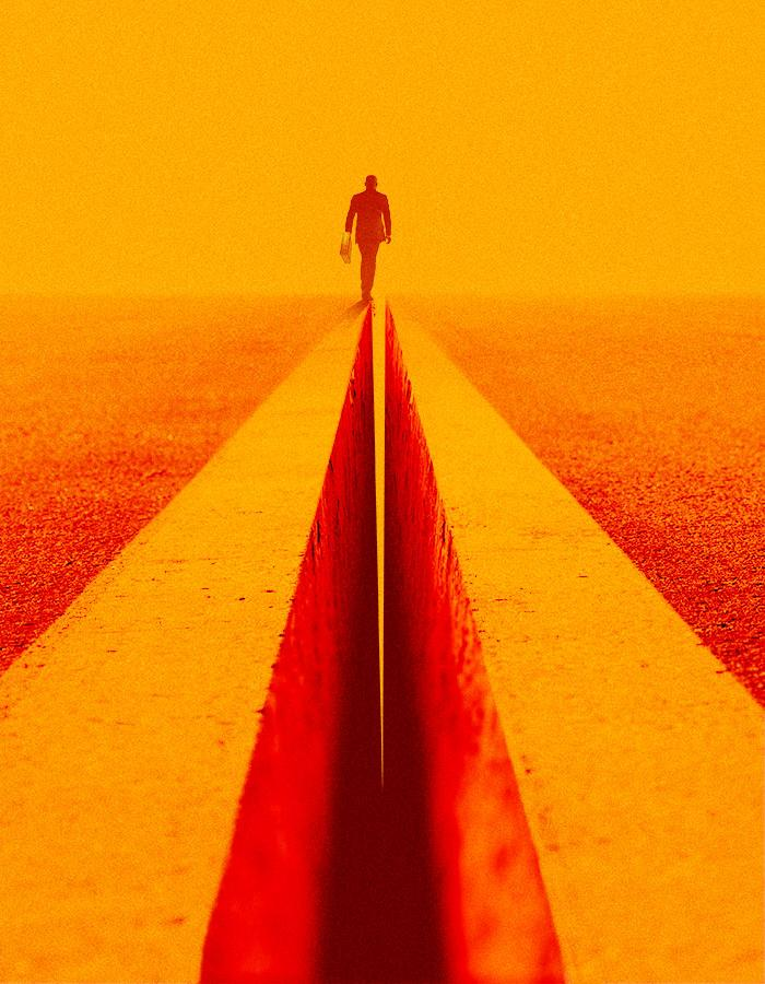 Death of a Salesman poster image.  A smartly dressed man in a suit is seen from behind walking into the distance. The ground has a large and deep crack running through it and he is walking along the left side of the edge of the gap.