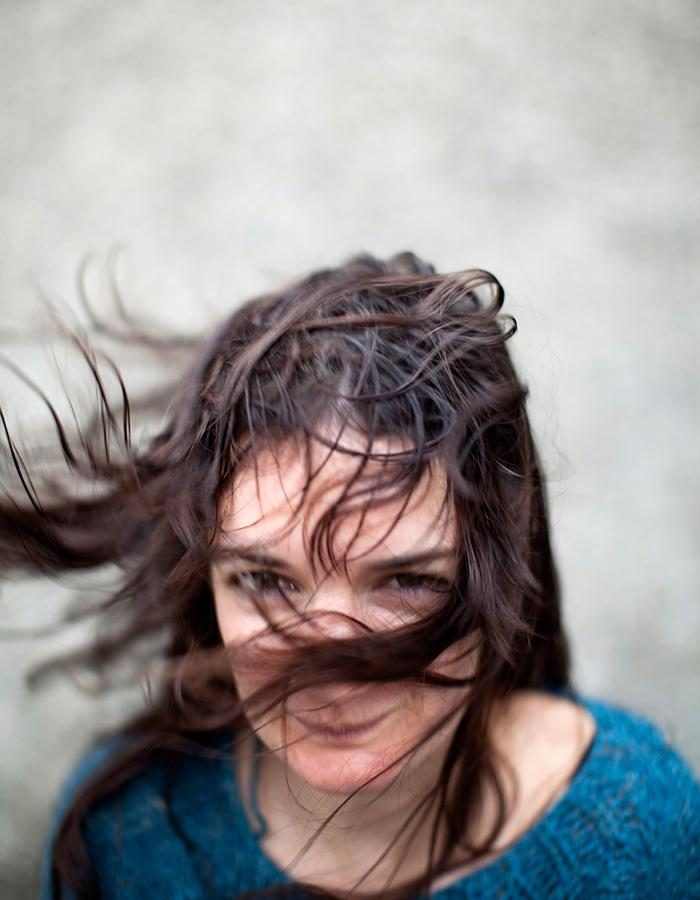 brunette women in a blue top with the wind blowing in here face that half of her face is covered.