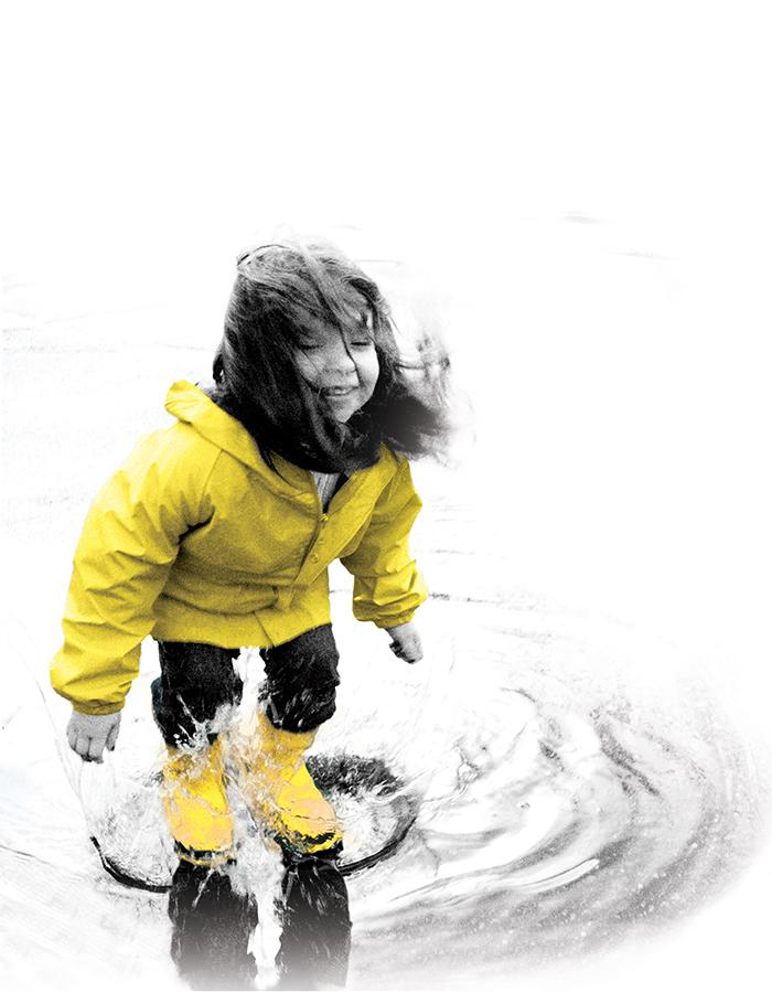 Little girl in a yellow jacket plays in a puddle