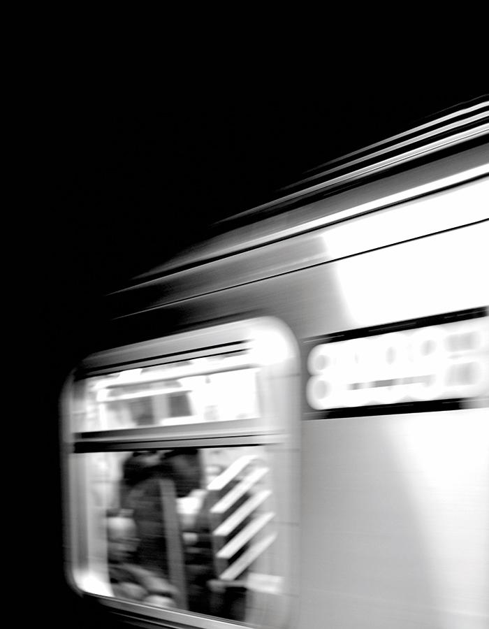Black and white image of a train window, train has been captured in motion so image is slightly blurred.