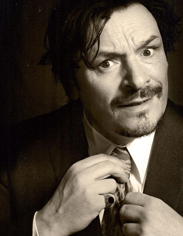 Julian Barratt looks quizzically at the camera while tightening his tie.