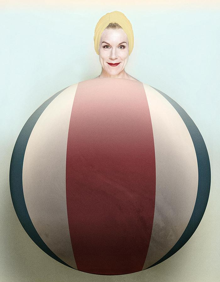 A smiling Juliet Stevenson is superimposed coming out the top of a striped oversized red, white and blue beach ball, almost as if the ball was her body.