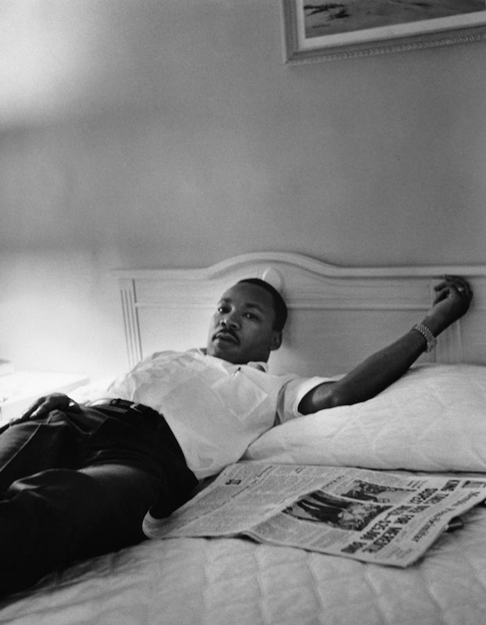 black and white image of dr martin luther king laying on a bed with newspapers beside him