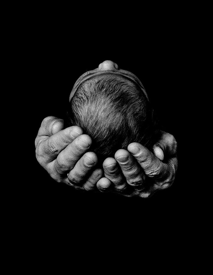 black and white image of two hands holding a babies head