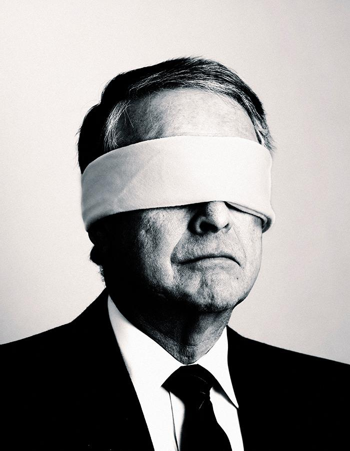 A man in a suite, with black tie, blindfolded