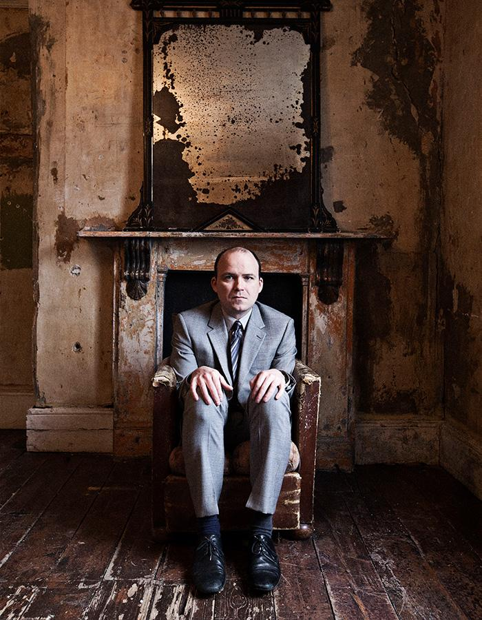 Rory Kinnear sits in a chair under a mirror in a derelict room