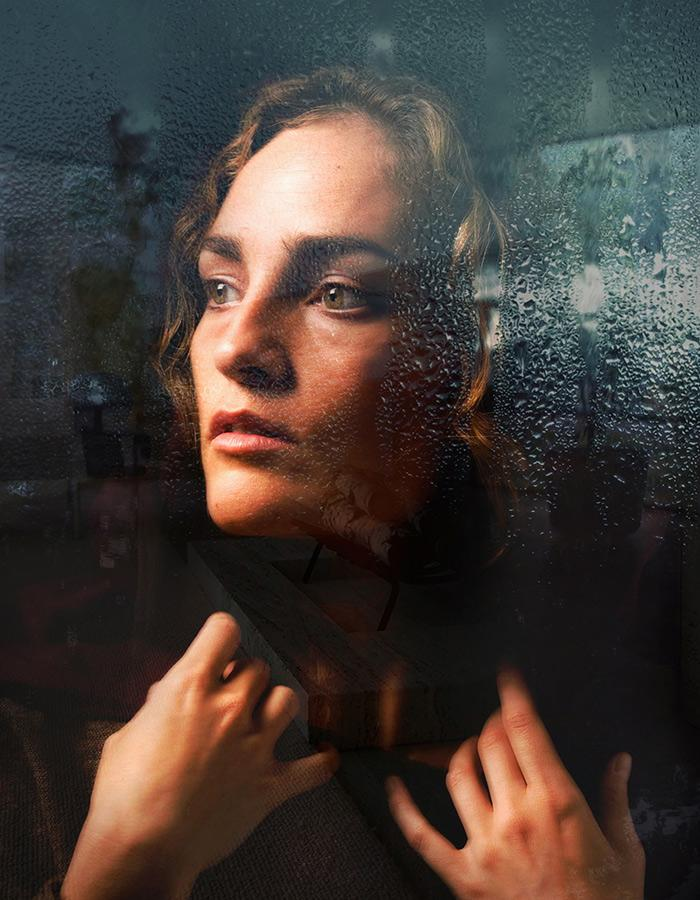 Woman looks pensively out window covered in rain drops