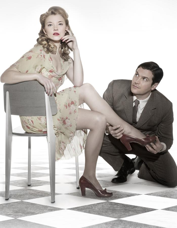 Natalie Dormer sits on a chair as Kieran Bew puts on her shoe