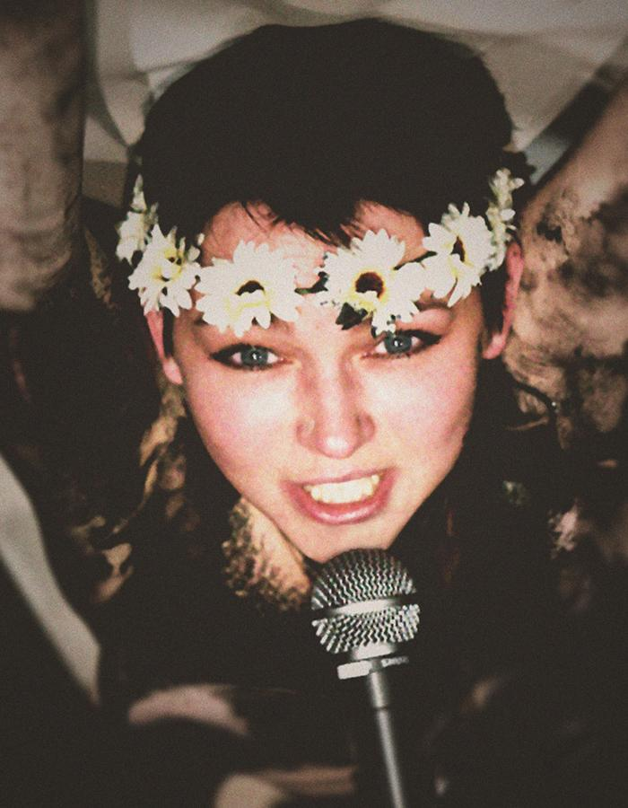 A girl with a flowered headband talks into a microphone