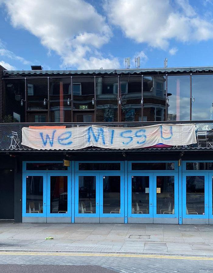 A banner with the words 'We Miss You' hangs outside the Young Vic theatre