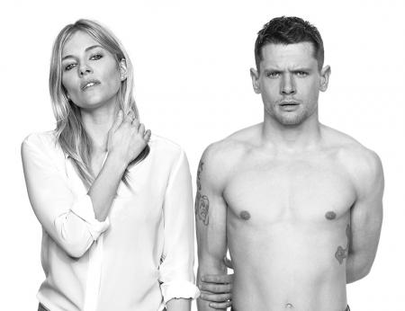 Sienna Miller in a casual white shirt and jeans next to Jack O'Connell bare chested in jeans on a white background