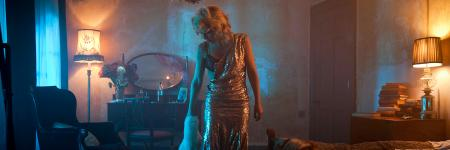Gillian Anderson on set in the Young Vic short film, The Departure. She stands in a glittering dress, with one strap hanging off her shoulder in a hazy, darkly-lit room.