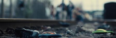 Shot from YV Short Film, Astoria. You can see a mix of abandoned shoes strewn along rail tracks, with out of focus figures slowly walking towards the camera.
