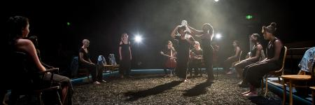 Production photo of Taking Part's parallel production of Yerma taken by Helen Murray. Two young female actors walk across a stage of what looks like mud with a puppet on one their shoulders. The rest of the cast sit on chairs either side of the stage focused on the action.