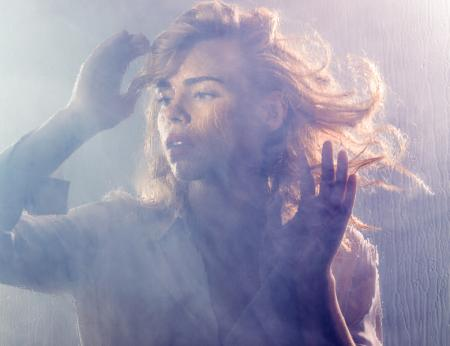 Billie Piper stands behind a misty pane of glass looking wistfully into the distance